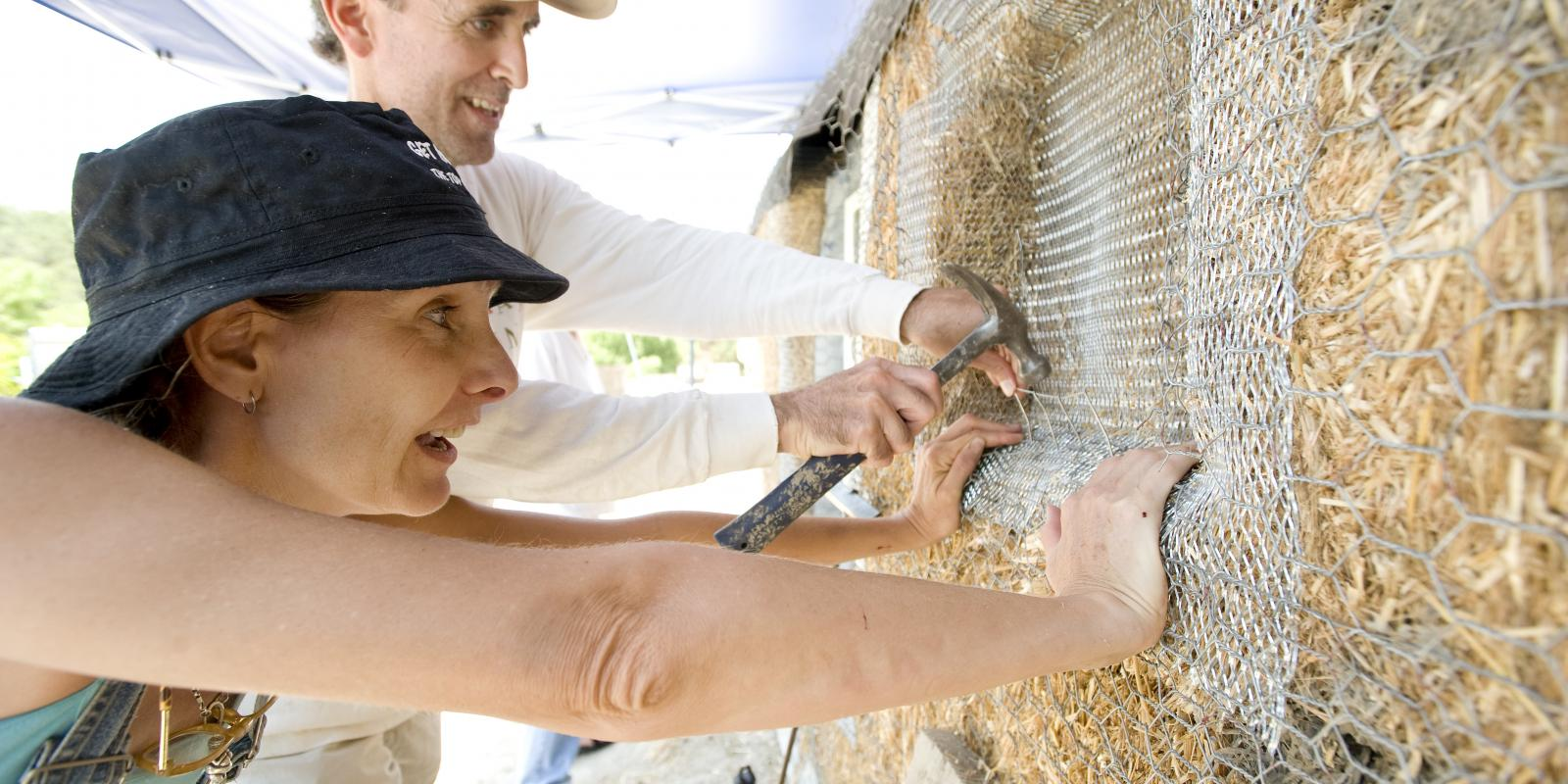 Sherrell Cuneo and Don Smith attatch chicken wire to a strawbale wall as part of The Solar Living Institute and Lyle Center's Sustainable Workshop, July 2008