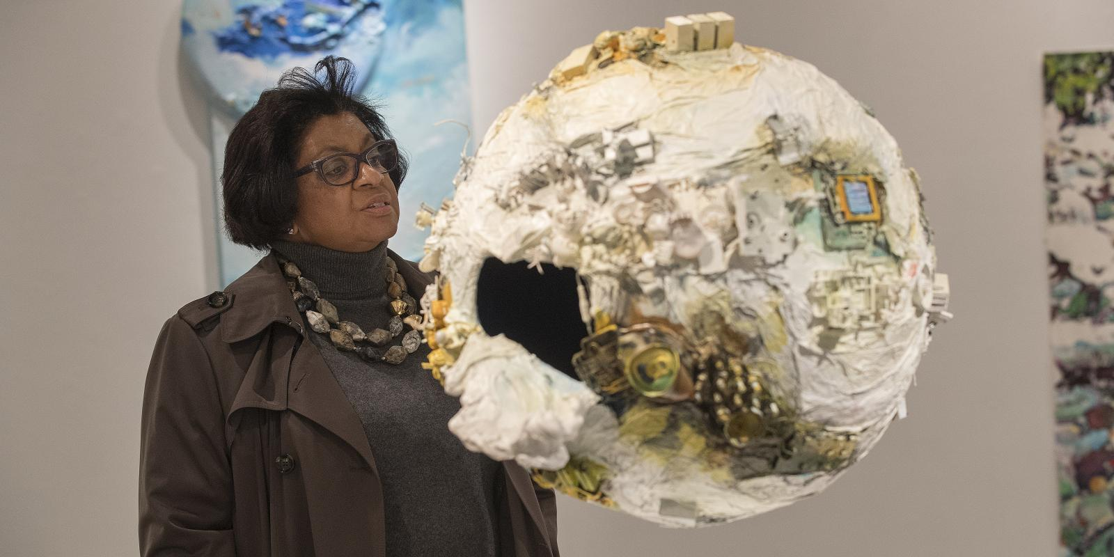 "University President Soraya Coley views ""Human Traces on Earth"" by Ann Phong, 2016 Art Faculty Show"