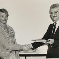 George Proctor (left) accepts the Dean's Award from Dean Marvin Malecha, 1989. (Image courtesy of George Proctor)