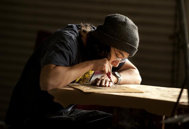 Diego Cardenas carves a piece of linoleum for his relief print making class, April 2011 (Tom Zasadzinski)